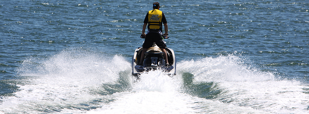 Man wearing yellow lifejacket heading out on his jetski